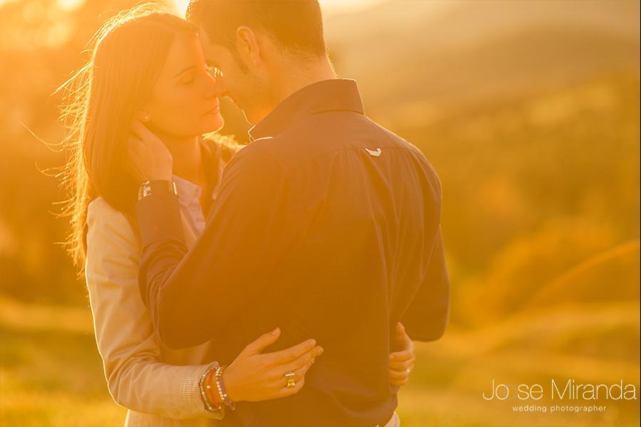 amor entre pareja de novios en preboda. hombre acariciando a mujer en el campo con la luz de la tarde