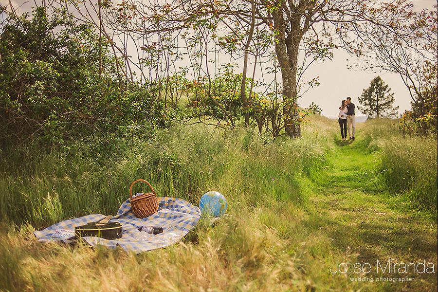 Fotografia de sesión de Pre-boda en el campo. Pareja de enamorados acercándose a un pinic.