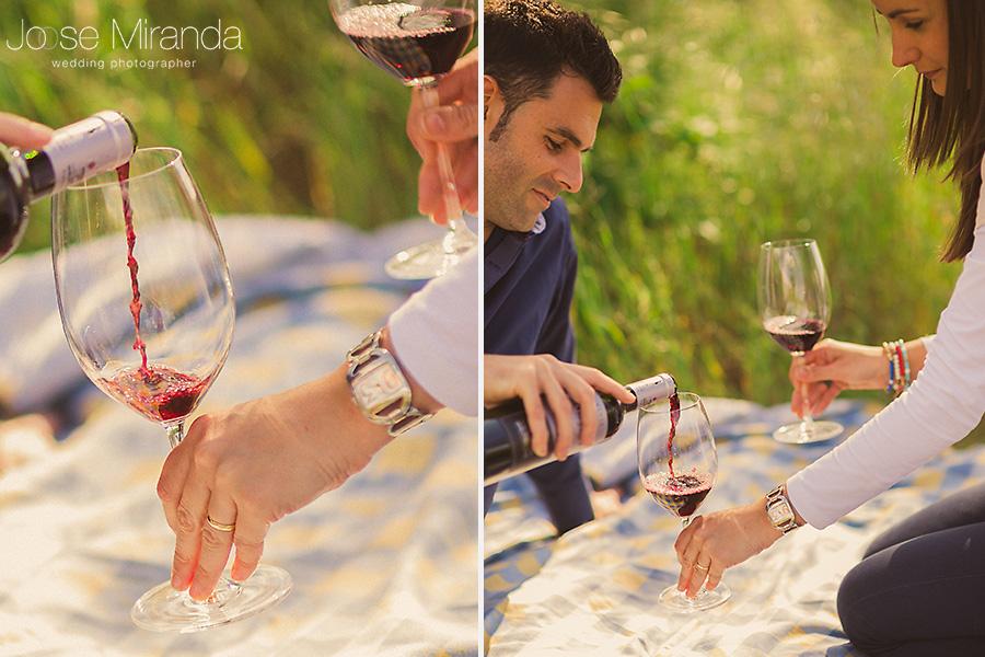 pareja de novios con copas de vino en un picnic. fotografia de pre-boda en el campo, El Centenillo, La Carolina.