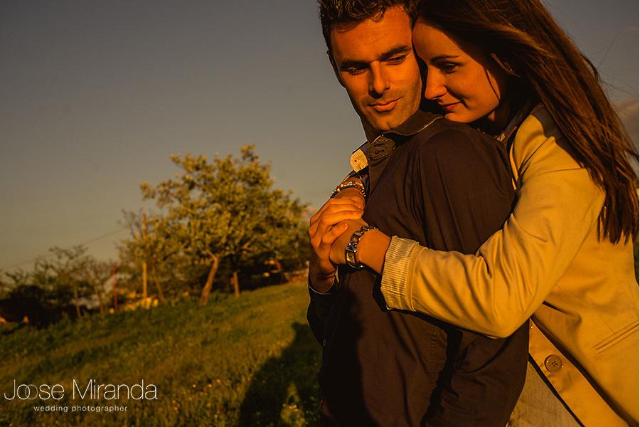 mujer de pelo oscuro y largo abrazada a hombre en el campo en una sesión preboda en el campo al atardecer