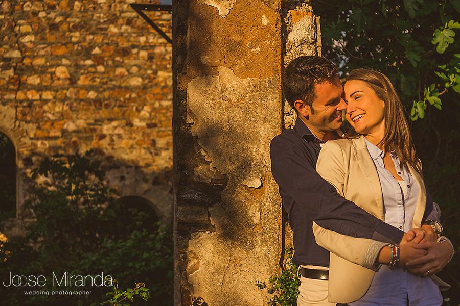 novio y novia iluminados por el sol en edificio de ladrillos