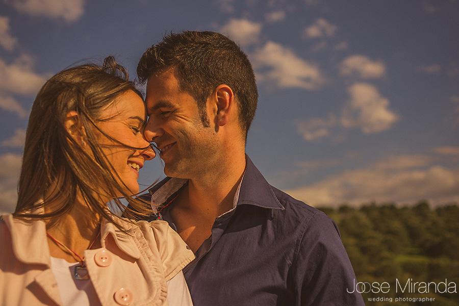 Fotografía de primer plano de novio y novia riéndose en sesión de pre-boda en el campo con cielo de nubes en El Centenillo, La Carolina