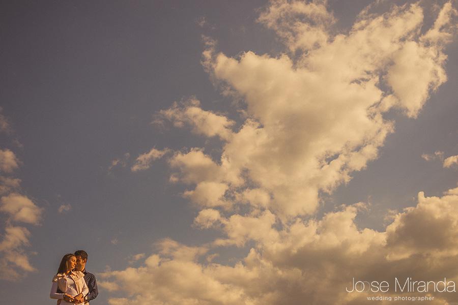 pareja en fotografia con nubes en sesión de pre-boda con ropa informal. El Centenillo, La Carolina