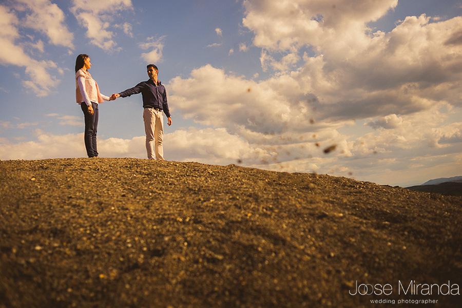 Fotografía de cuerpo entero de novios en pre-boda sobre montículo de tierra y cielo con nubes en El Centenillo, La Carolina