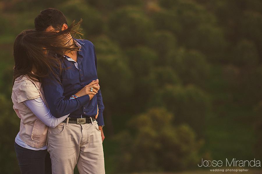 Abrazo de novios en sesión de pre-boda con manos entrecruzadas en el campo en El Centenillo, La Carolina
