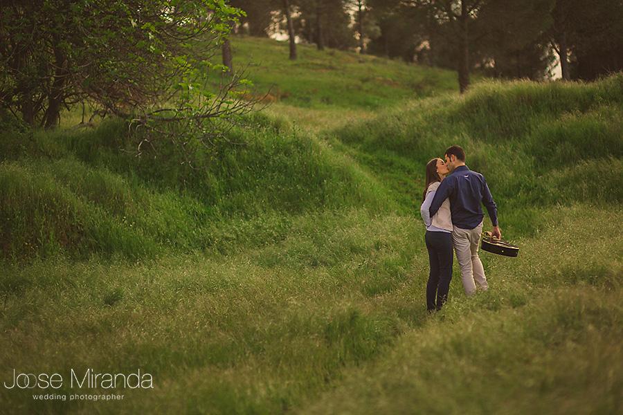 Fotografia en prado verde y árboles con novios en sesión de pre-boda besándose en El Centenillo, La Carolina