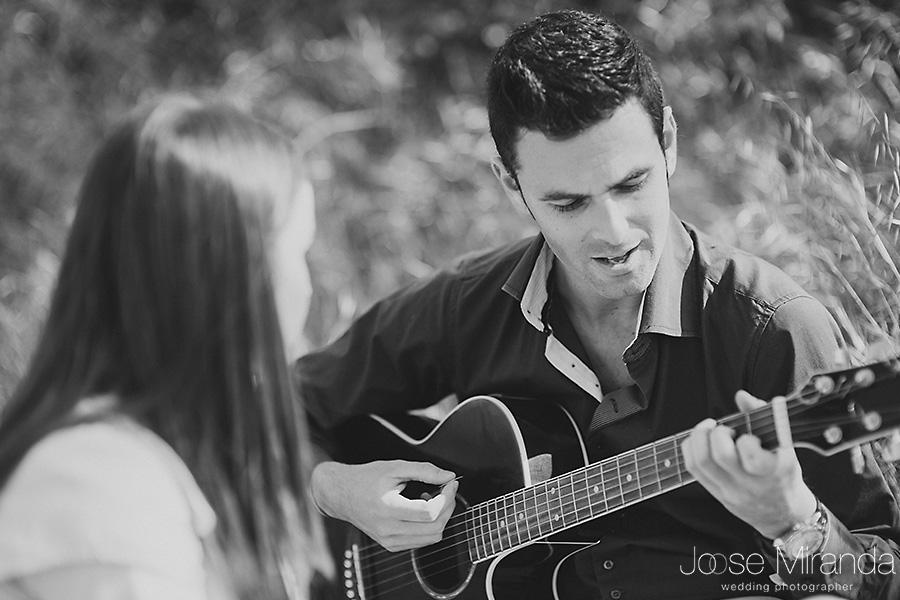 Retrato de novio tocando la guitarra en sesión de fotos de pre-boda en un picnic en el campo de El Centenillo, La Carolina