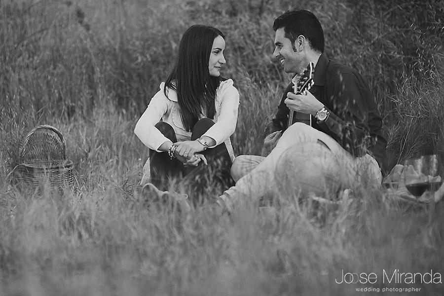 Fotografía en blanco y negro de pre-boda en un picnic con vino, cesta y novio tocando la guitarra a la novia