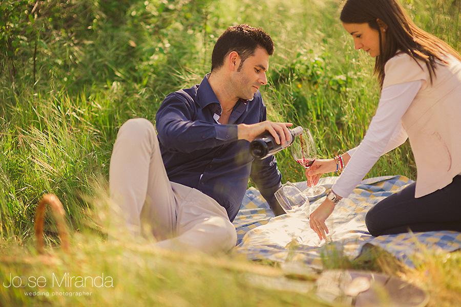Pareja con copas de vino tinto en foto de pre-boda en un picnic en El Centenillo, La Carolina