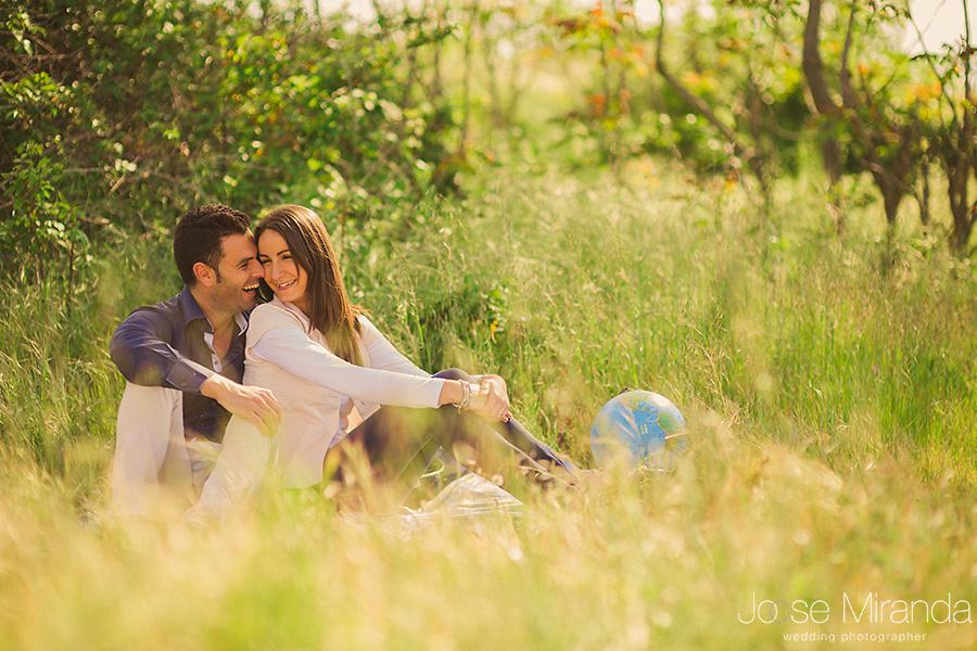 Fotografía de novios riéndose en un picnic  con vino y la bola del mundo. Sesión de pre-boda en el campo