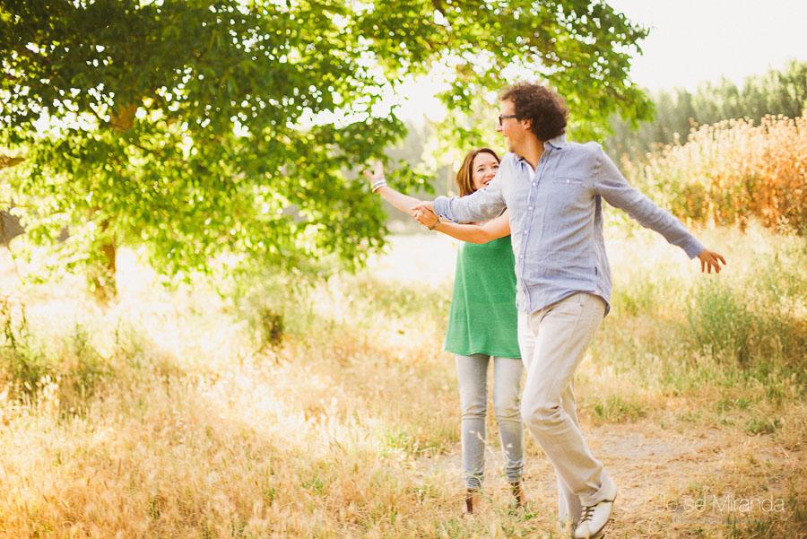 pareja de novios saltando en el campo mientras sonrien