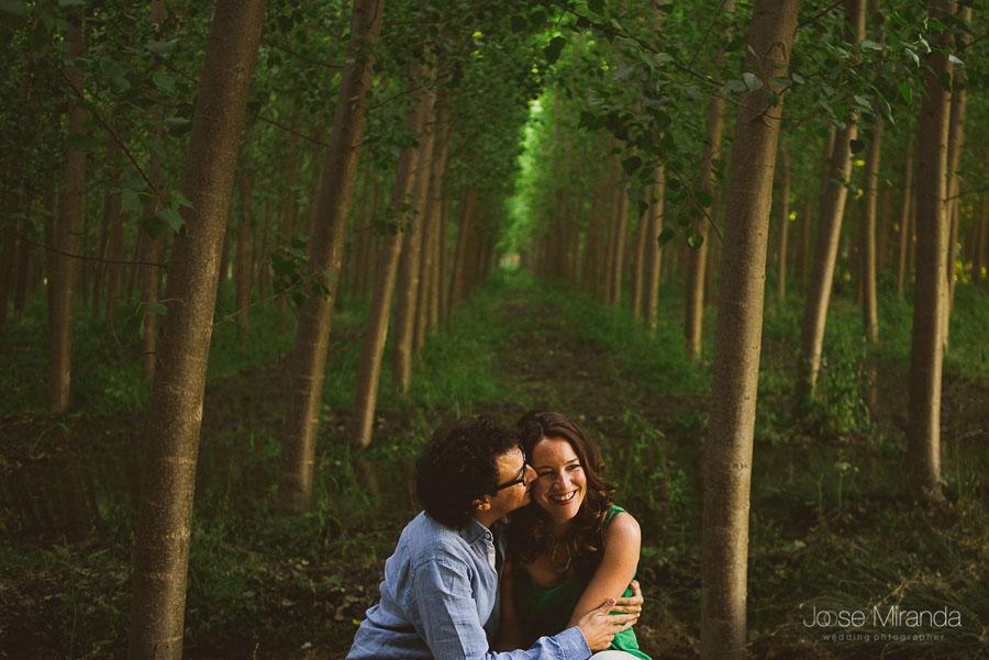pareja en campo de alamos verdes y luces que entran entre los árboles
