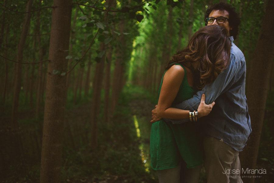 novios abrazados mientras sonríen en bosque de álamos con luces que penetran por detrás