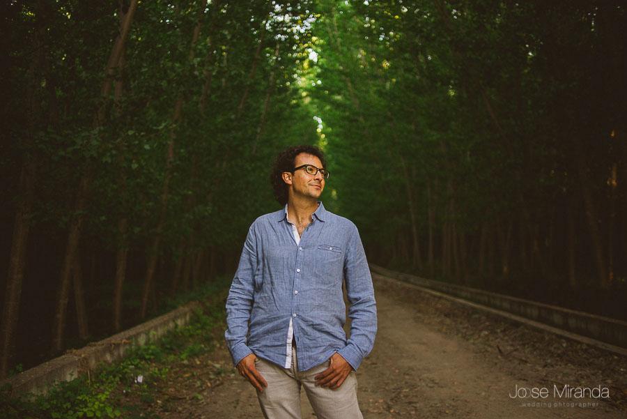 fotografia de novio en sesión de pre-boda con gafa y camisa azul en un camino del campo