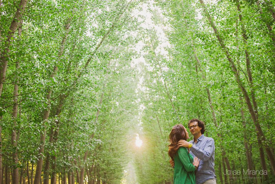 novio apartándole el pelo a novia en pre-boda en un camino entre árboles en Granada
