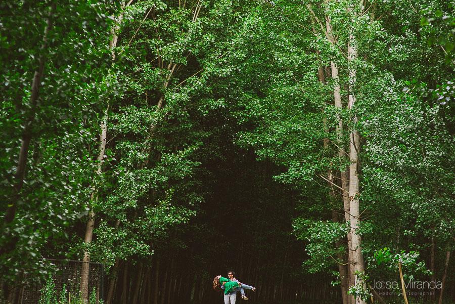 novio levantando a novia al final del camino entre bosque de álamos en foto antes de la boda en Granada