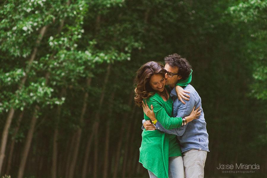 novios abrazados y dándose besos mientras pasean por el camino de los áboles altos y verdes