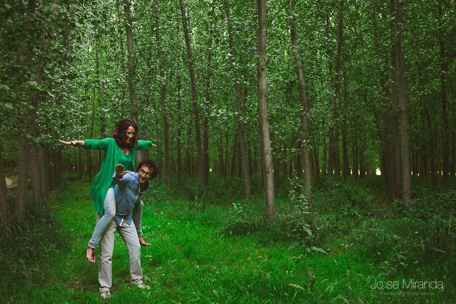 novia sobre novio a horcajadas mientras juegan en campo de arboles en verano