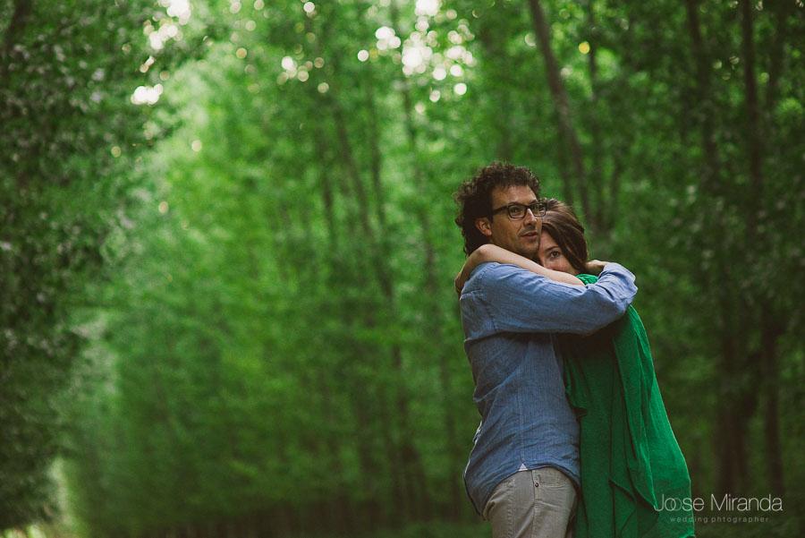 pareja abrazados mirando al frente en escenario de árboles verdes en sesión de pre-boda en el campo