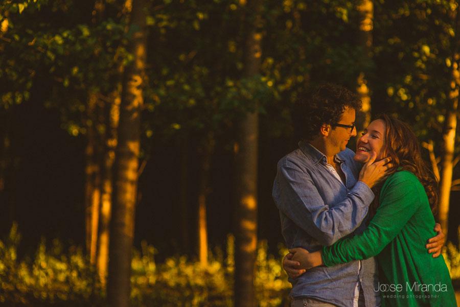 pareja de enamorados mirandose en arboleda con las luces del atardecer en Granada