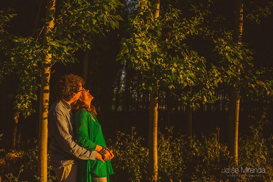 sonrisas entre parejas de enamorados sobre escenario de árboles enfilados al borde de un camino
