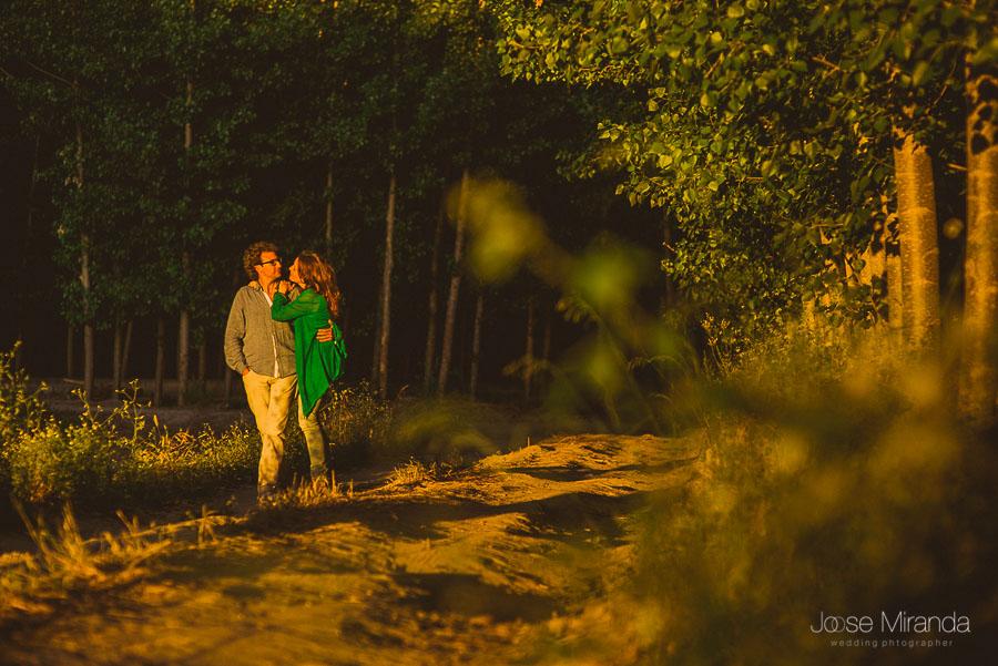 pareja abrazada con look informal de vaqueros en camino de árboles y luces bajas del atardecer
