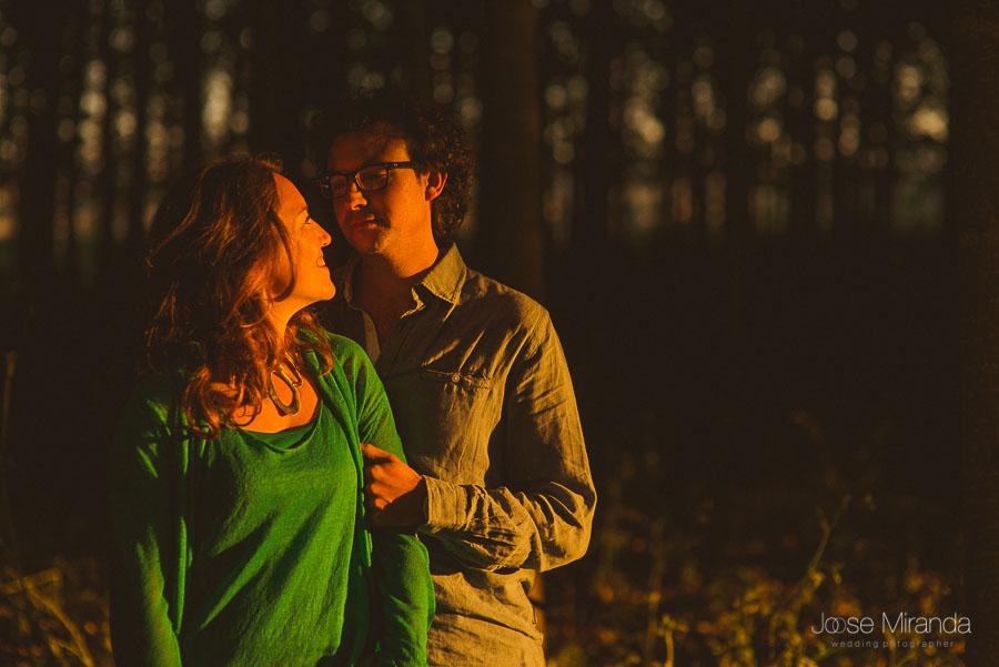 novia mirando a su pareja iluminada por el sol con camiseta verde con vistas al bosque
