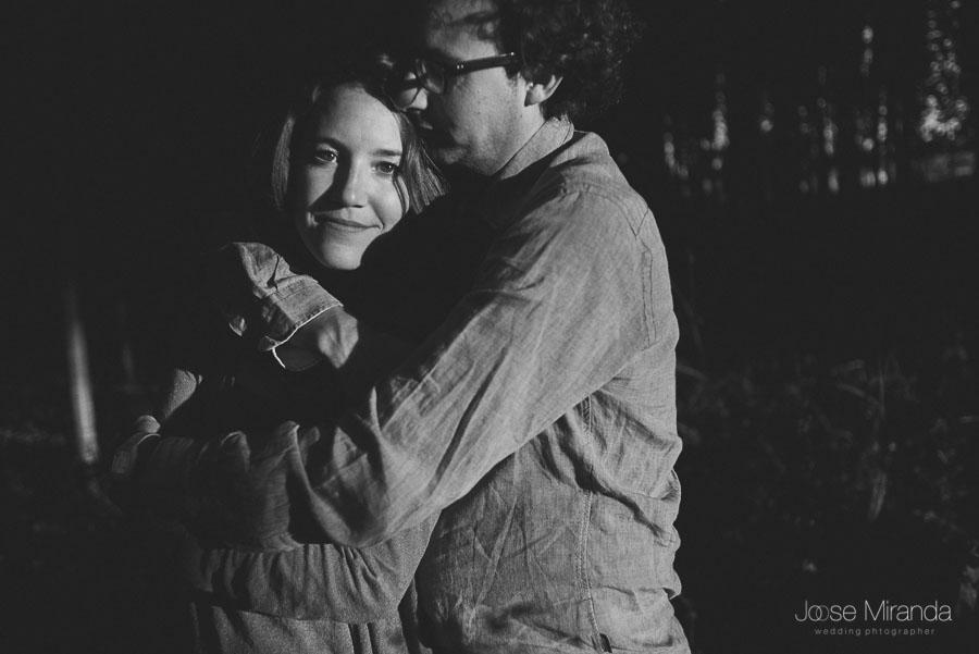 pareja enamorada y mujer mirando a la cámara en sesión de fotografias de pre-boda en el campo en Granada