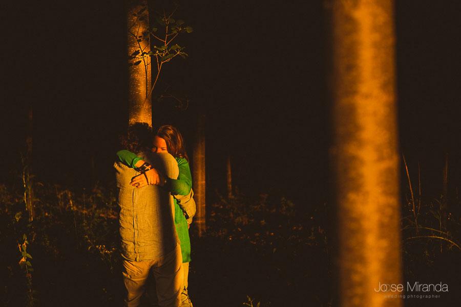 abrazo de novia a novio entre bosque de árboles con luces oscuras y claras en sesion de fotos
