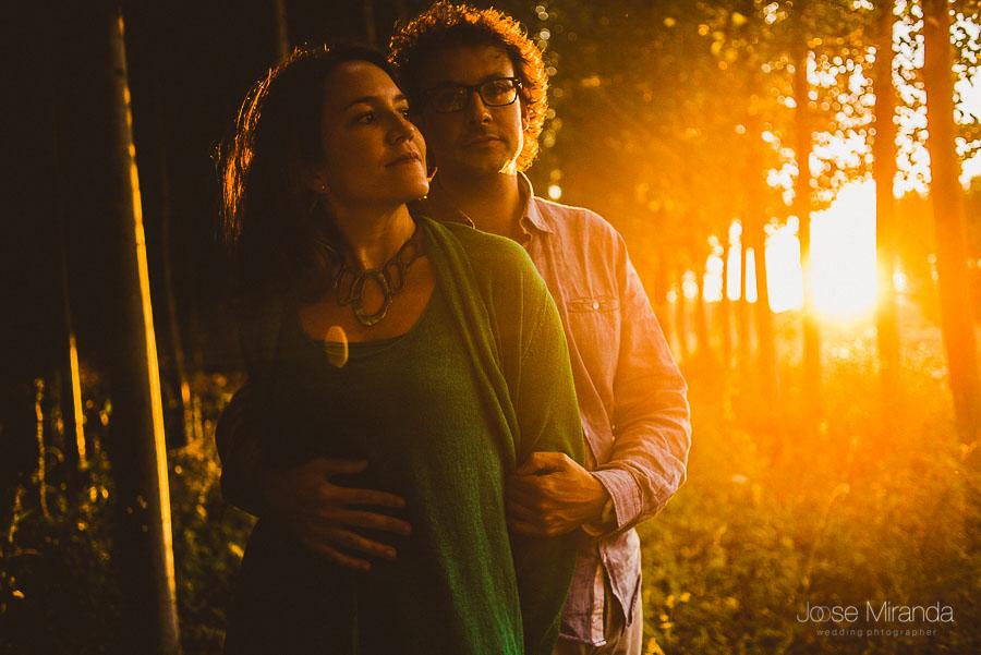 pareja con ejemplo de pre-boda en el bosque con luces bajas de la tarde y sol por detras
