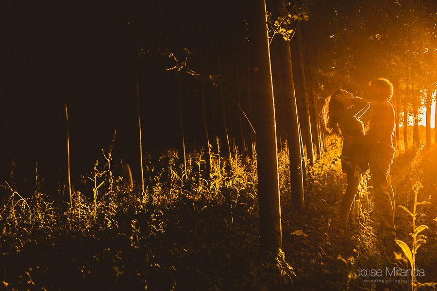 contraluz en el bosque mientras cae el sol y novia se arregla el pelo y novio la abraza