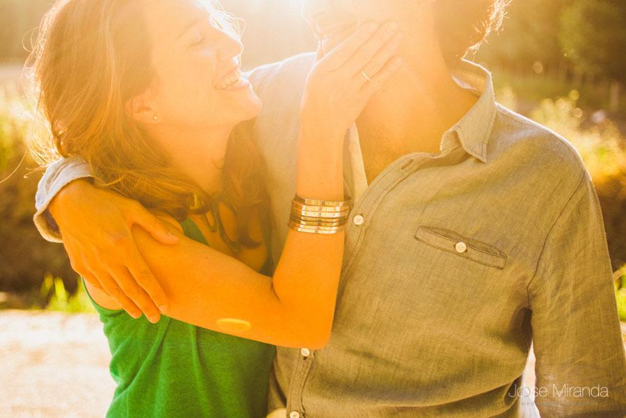 novia con pulseras acariciando a su novio en las luces del atardecer