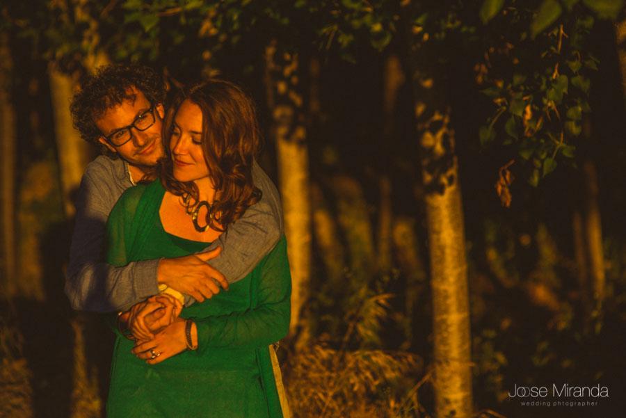 hombre abrazando a mujer enamorados con luces calidas y sol bajo en un bosque