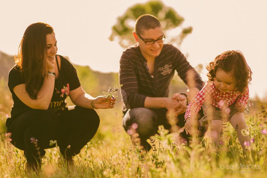 contraluz de unos padres y su hija jugando en el campo con flores en una sesión de preboda de Jose Miranda Fotografia y boda en Jaén