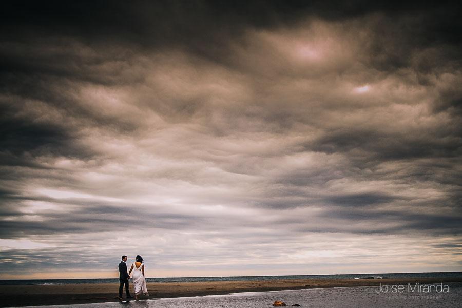Pareja de novios paseando por la playa de monsul en Alamería en una sesión post-boda de Jose miranda fotografia