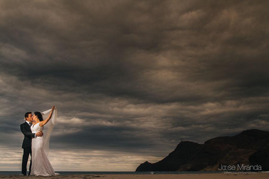 Pareja de novios besándose con el velo en las manos de la novio alzándolo en la playa de monsul en almería con el cabo de gata al fondo el cielo atormentado en una fotografia de jose miranda boda