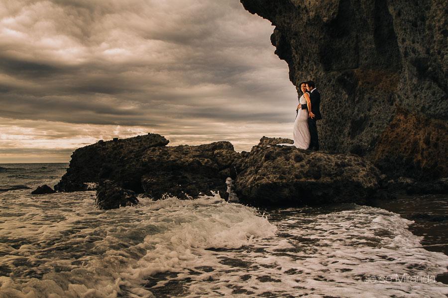 Novios abrazados sobre las rocas de la duna de Mónsul en el cabo de gata de almería con el mar en primer plano y el cielo atormentado en una fotografia de jose miranda boda en Jaén