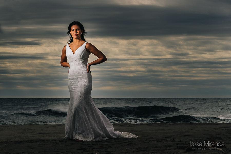 Novia posando en la playa de el Mónsul en un día de boda con el cielo atormentado y ella en primer plano con su vestido pronovias
