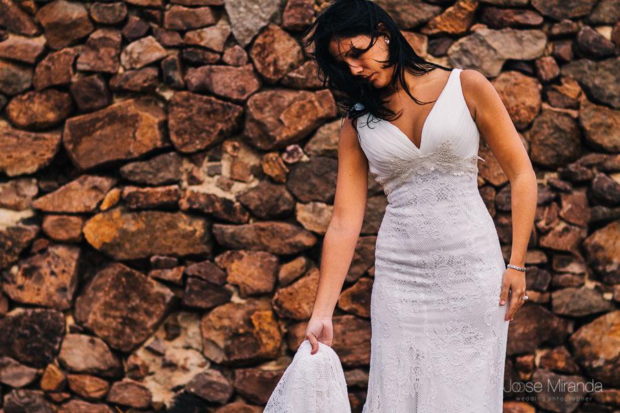 Novia con el pelo suelto en la cara por el viento cogiendo la cola de su vestido de novia de pronovias con una pared de  piedra al fondo en el cabo de gata de almería