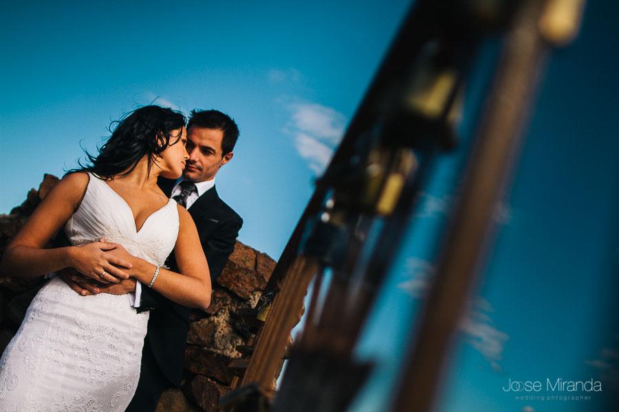 pareja de novios abrazados y mirandose en segundo plano y los barrotes del mirador dela cabo de gata con candados en primer plano sobre un cielo azul