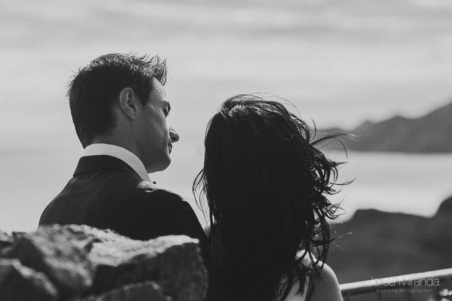 novio mirando a la novia desde atras y de fondo se ve el paisaje del cabo de gata y el mar de almería en una foto de boda