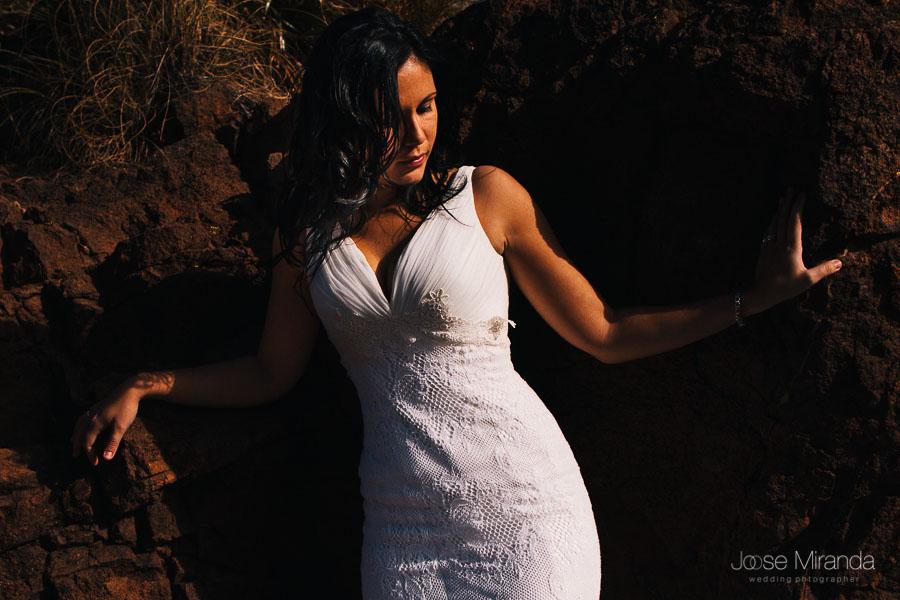 Novia entres las rocas con el sol iluminando un lado de su cara y el otro tapado por el pelo que le cae por delante en el cabo de gata de Almería
