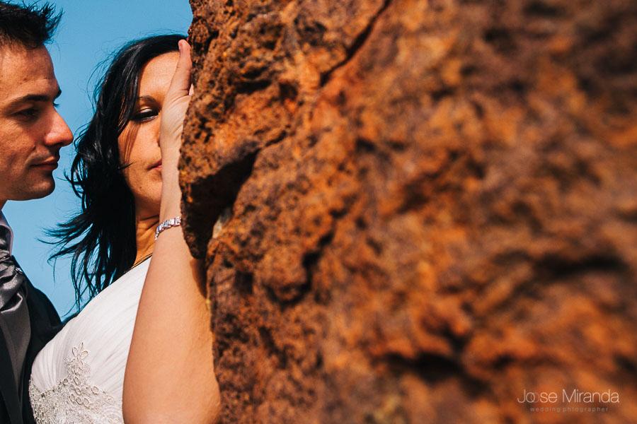 Novia sobe una roca mientras el novio se acerca a besarla roca roja y cielo azul en el cabo de gata almería