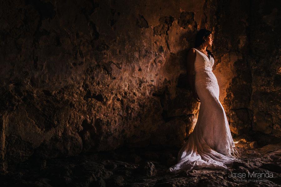 Novia con vestido de encaje de algodón iluminada entre las rocas con mirada pensativa. Sesión de fotografías de post-boda en la torre de la playa del Playazo.