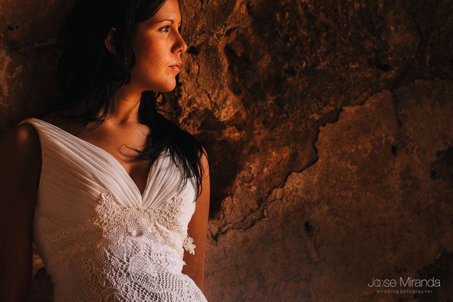 Fotografía de novia con vestido de higar novias con escote de pico drapeado, pelo suelto y maquillaje sencillo. Sesión de post-boda en un día soleado en la Playa del Playazo.