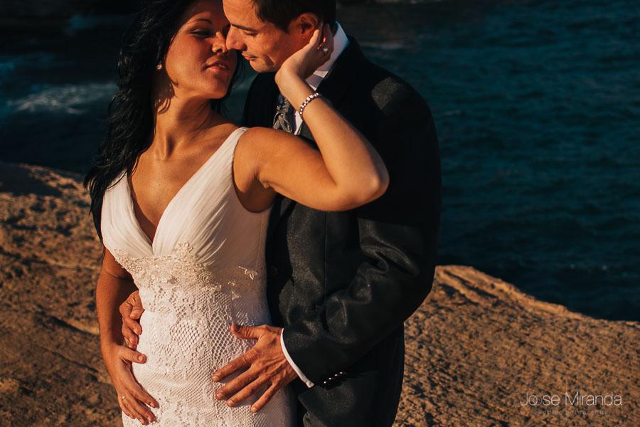 Fotografia de pareja novios en post-boda. Novia con vestido de encaje de algodón y aplique en el pecho y novio con camisa de Victorio y Lucchino en el acantilado de la playa del Playazo en Cabo de Gata Almería.