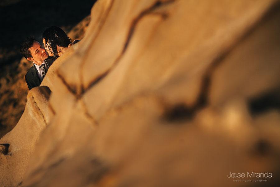 Pareja de novios besándose tapados por formación rocosa del cabo de gata almería en fotografía de boda en jaén de jose miranda