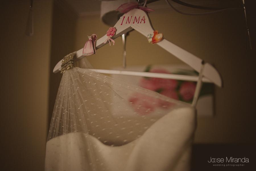 Vestido de novia de Jesús Peiro colgado de una percha con el nombre de la novia, Inma, en una fotografia de boda en Linares