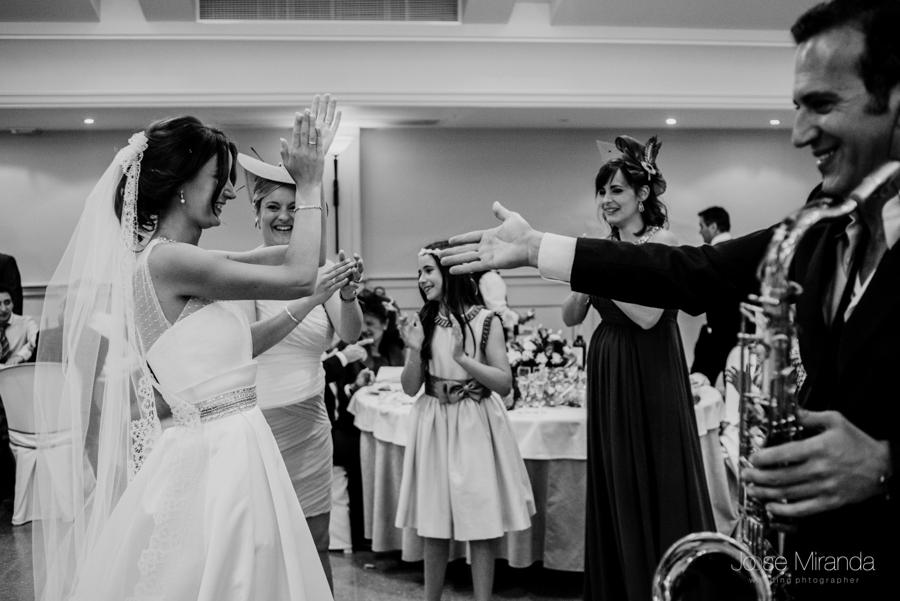 Novia saludando a los invitados de la boda y al saxofonista que tocó durante el banquete en La Hacienda El Campero de Linares en una fotografía de Jose Miranda
