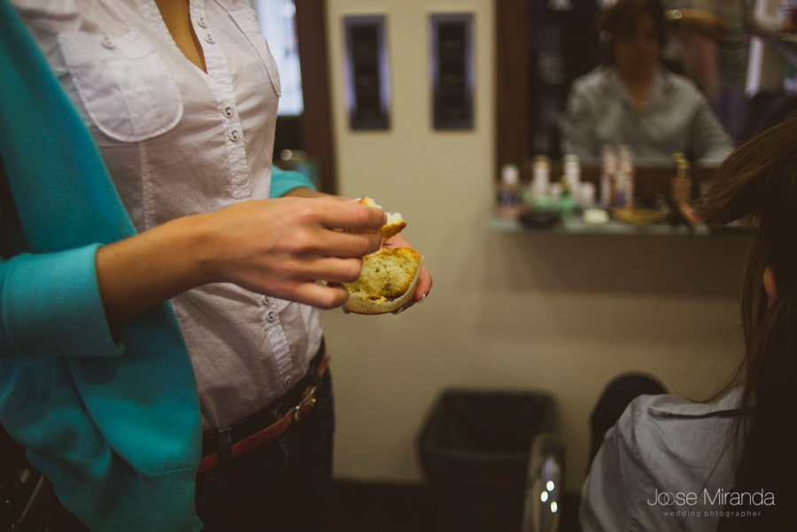 La novia desayunando en la peluquería de Rebeca Caballero en Linares, mientras peinan a la hermana de la novia
